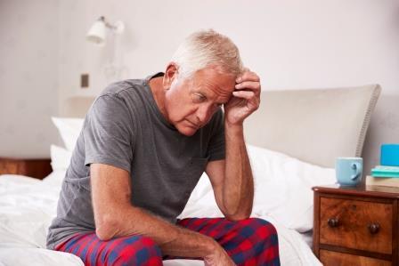 senior-man-sitting-on-bed-at-home